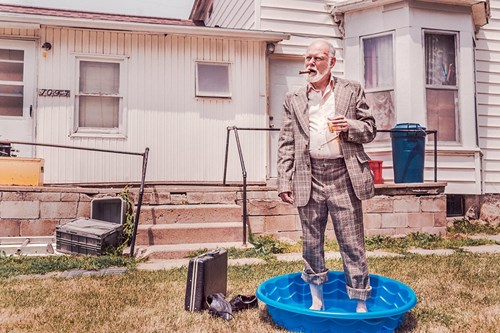Business man standing in wading pool - represents lack of work - life balance