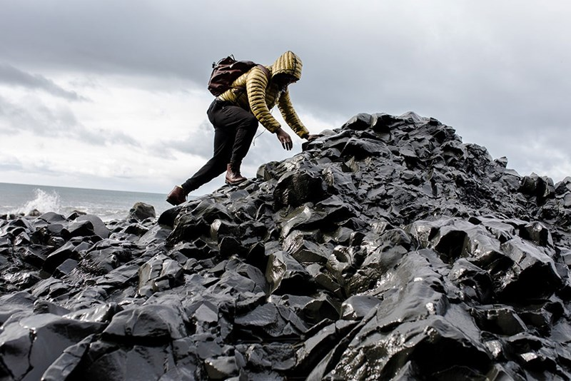 man wearing a backpack in trousers, leather shoes, and puffer coat climbing a rocky section of shoreline by the ocean