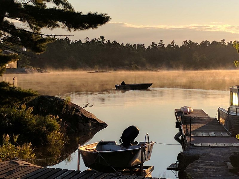 Sunrise over a lake and a fisherman returning to the dock
